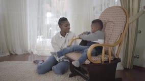 Mujer afroamericana linda alegre que juega con su pequeño hijo lindo y divertido que se sienta en una mecedora en sala de estar almacen de video