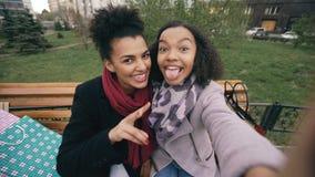 Mujer afroamericana linda dos que toma el selfie en smartphone con los panieres y la sonrisa Novias que se sientan encendido almacen de metraje de vídeo