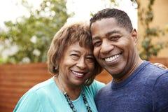 Mujer afroamericana mayor y su hijo envejecido medio que sonríen a la cámara, a la cabeza y a los hombros, cierre para arriba imagen de archivo