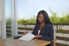 Mujer afroamericana negra atractiva joven que se sienta al aire libre en el trabajo de la cafetería ocupado y feliz fotos de archivo
