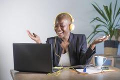 Mujer afroamericana negra feliz joven que escucha la música con los auriculares emocionados y el trabajo alegre en el escritorio  fotografía de archivo