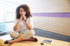 Mujer afroamericana ocasional vestida que sienta legged cruzado Fotos de archivo