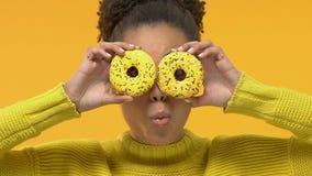 Mujer afroamericana positiva que lleva a cabo el frente de ojos, humor juguetón de los anillos de espuma, bromeando almacen de metraje de vídeo