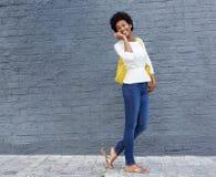 Mujer afroamericana que camina y que habla en el teléfono móvil Imágenes de archivo libres de regalías