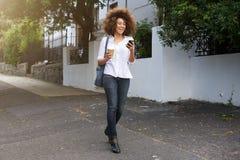 Mujer afroamericana que camina y que mira el teléfono móvil Imagen de archivo libre de regalías