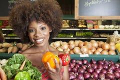 Mujer afroamericana que celebra los paprikas y las verduras en el supermercado Foto de archivo