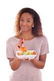 Mujer afroamericana que come la ensalada, aislada en el backgroun blanco Imagenes de archivo