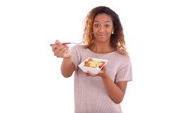 Mujer afroamericana que come la ensalada, aislada en el backgroun blanco Fotos de archivo