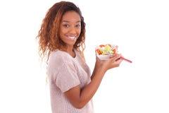 Mujer afroamericana que come la ensalada, aislada en el backgroun blanco Fotos de archivo libres de regalías