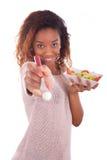 Mujer afroamericana que come la ensalada, aislada en el backgroun blanco Foto de archivo libre de regalías