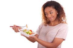Mujer afroamericana que come la ensalada, aislada en el backgroun blanco Imágenes de archivo libres de regalías