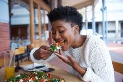 Mujer afroamericana que come la pizza en el restaurante al aire libre Foto de archivo
