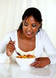 Mujer afroamericana que come un tazón de fuente de cereales Fotografía de archivo