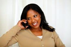 Mujer afroamericana que conversa en el teléfono móvil Imágenes de archivo libres de regalías