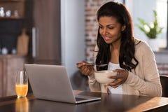 Mujer afroamericana que desayuna y que usa el ordenador portátil en la cocina Imagen de archivo libre de regalías
