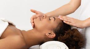 Mujer afroamericana que disfruta de masaje facial antienvejecedor imagen de archivo