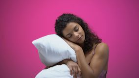 Mujer afroamericana que duerme en la almohada aislada en el fondo rosado, resto almacen de metraje de vídeo