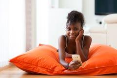 Mujer afroamericana que envía un mensaje de texto en un teléfono móvil Fotografía de archivo