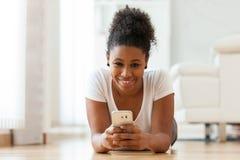 Mujer afroamericana que envía un mensaje de texto en un teléfono móvil Foto de archivo