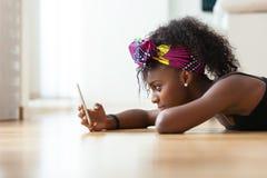 Mujer afroamericana que envía un mensaje de texto en un teléfono móvil imágenes de archivo libres de regalías