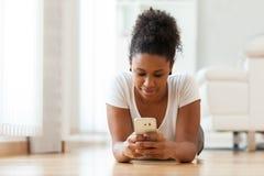 Mujer afroamericana que envía un mensaje de texto en un teléfono móvil Imagen de archivo