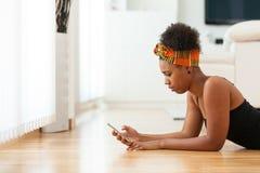 Mujer afroamericana que envía un mensaje de texto en un teléfono móvil Fotografía de archivo libre de regalías