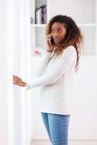 Mujer afroamericana que habla en un teléfono móvil - personas negras Fotos de archivo libres de regalías