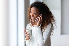 Mujer afroamericana que habla en un teléfono móvil - personas negras Imagenes de archivo