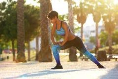 Mujer afroamericana que hace ejercicio que estira agazapado Fotografía de archivo