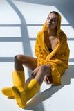 Mujer afroamericana que lleva el impermeable amarillo y las botas de goma que se sientan en piso fotos de archivo libres de regalías
