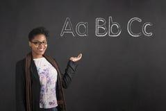 Mujer afroamericana que muestra el alfabeto de ABC contra la pizarra Fotografía de archivo