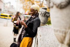 Mujer afroamericana que presenta afuera con el móvil Foto de archivo libre de regalías