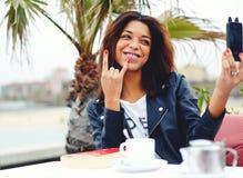 Mujer afroamericana que se divierte mientras que se fotografía con el teléfono elegante en cafetería Imagen de archivo libre de regalías