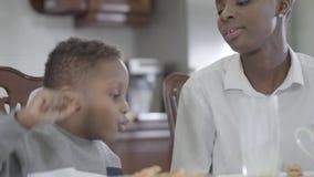 Mujer afroamericana que se sienta con su peque?o hijo por la tabla que juega as? como las galletas Desayuno sano de la familia almacen de metraje de vídeo