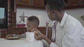 Mujer afroamericana que se sienta con su pequeño hijo por la tabla que juega las galletas en la placa Mamá e hijo de la relación almacen de video