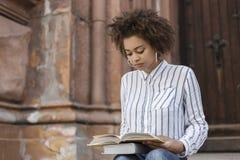 Mujer afroamericana que se sienta en la calle y que lee un libro En los libros de las piernas Hay un edificio al lado de una much imagen de archivo