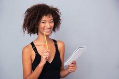 Mujer afroamericana que sostiene el cuaderno con el lápiz o Fotografía de archivo libre de regalías