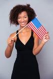 Mujer afroamericana que sostiene la bandera de los E.E.U.U. Fotos de archivo