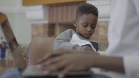 Mujer afroamericana que trabaja en el ordenador portátil y su pequeño hijo lindo que juegan con los juguetes cerca en sala de est almacen de video