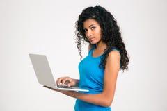 Mujer afroamericana que usa el ordenador portátil y mirando la cámara Fotografía de archivo libre de regalías