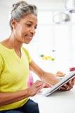 Mujer afroamericana que usa la tableta de Digitaces en casa Imagenes de archivo
