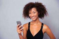 Mujer afroamericana que usa smartphone Imagen de archivo