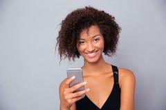 Mujer afroamericana que usa smartphone Foto de archivo libre de regalías