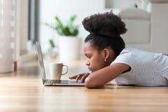 Mujer afroamericana que usa un ordenador portátil en su sala de estar - negro Imagen de archivo