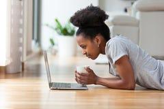 Mujer afroamericana que usa un ordenador portátil en su sala de estar - negro Fotos de archivo libres de regalías