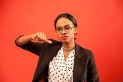 Mujer afroamericana seria con su pulgar abajo Fondo rojo Fotografía de archivo libre de regalías