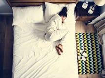 Mujer afroamericana sola en cama que duerme solamente fotografía de archivo