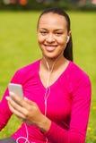 Mujer afroamericana sonriente con smartphone Imagen de archivo