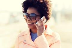 Mujer afroamericana sonriente con smartphone Foto de archivo