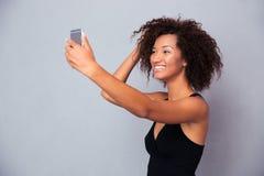 Mujer afroamericana sonriente que hace la foto del selfie Imagen de archivo libre de regalías